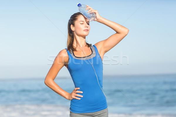 Beautiful fit woman putting water bottle in her head  Stock photo © wavebreak_media
