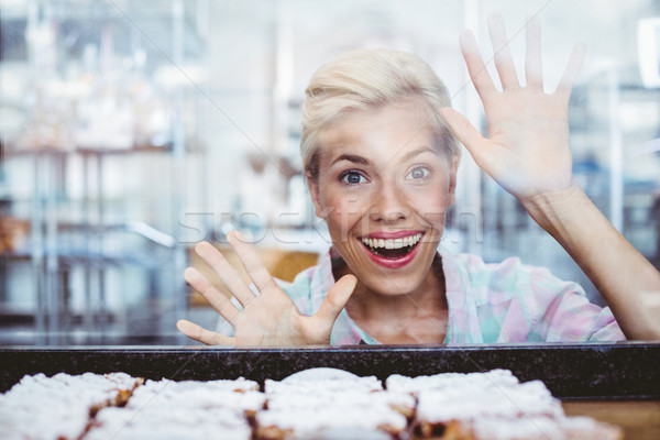 Astonished pretty woman looking at cup cakes  Stock photo © wavebreak_media