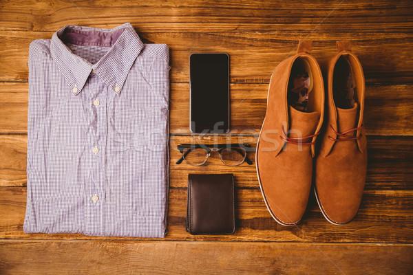 Shirt scarpe occhiali portafoglio smartphone tavolo in legno Foto d'archivio © wavebreak_media