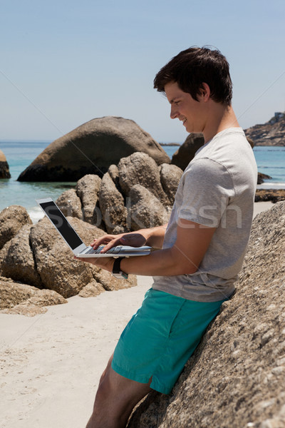 Man rotsen met behulp van laptop zee kust Stockfoto © wavebreak_media