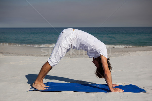Man performing yoga at beach Stock photo © wavebreak_media