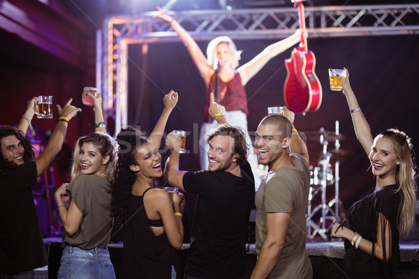 Stock photo: Portrait of cheerful fans with female performer on stage