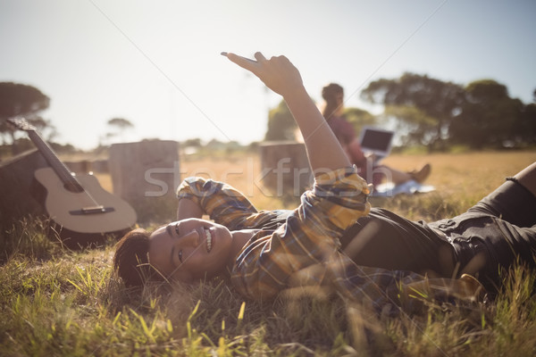 Portrait of smiling young man using mobile phone while lying on field Stock photo © wavebreak_media