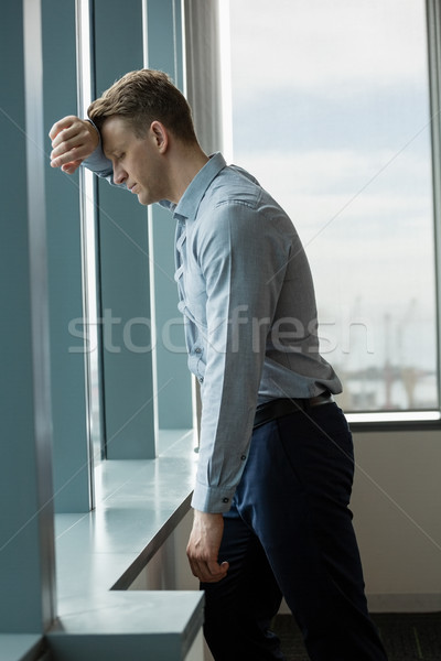 Thoughful executive leaning on window Stock photo © wavebreak_media