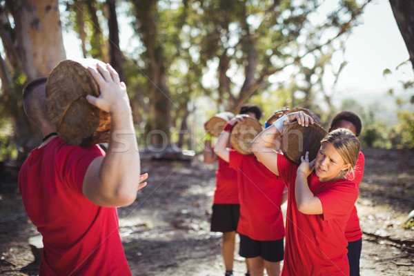 Trainer and kids carrying wooden logs during obstacle course training Stock photo © wavebreak_media