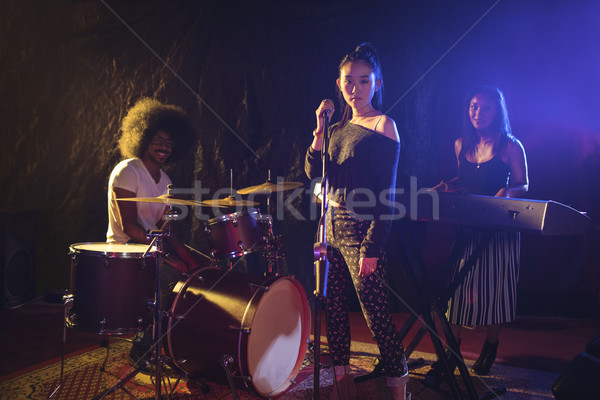 Confident musicians and singer performing on illuminated stage in nightclub Stock photo © wavebreak_media