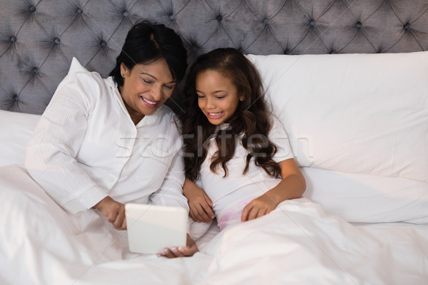 High angle view of smiling grandmother and granddaughter using digital tablet on bed Stock photo © wavebreak_media