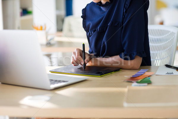 Female executive working over laptop and graphic tablet at her desk Stock photo © wavebreak_media
