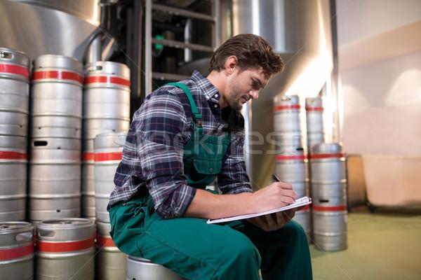 Worker writing on paper while sitting on keg at warehouse Stock photo © wavebreak_media