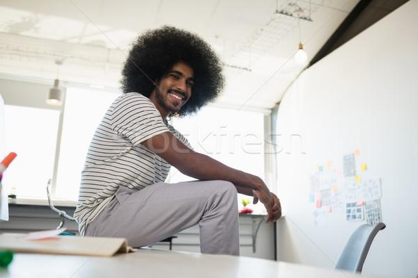 Portrait of smiling man relaxing on desk in creative office Stock photo © wavebreak_media