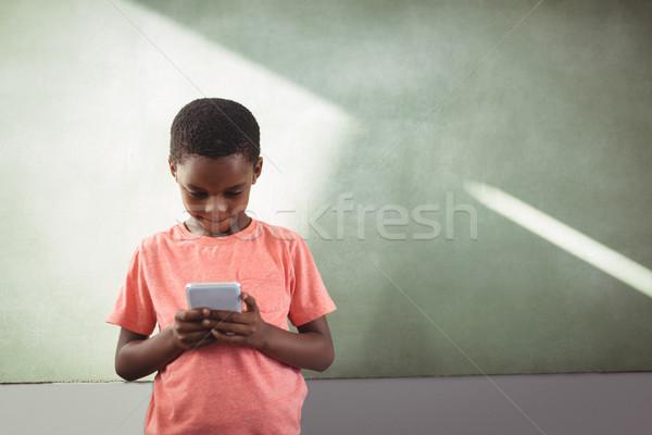 Boy using cellphone against greenboard in school Stock photo © wavebreak_media