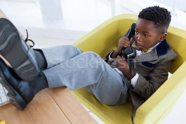 High angle view of boy imitating as businessman talking on landline phone Stock photo © wavebreak_media