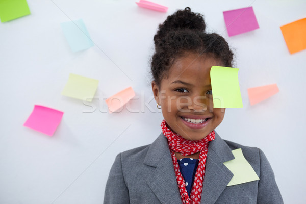 Portrait of smiling businesswoman with sticky notes stuck on head Stock photo © wavebreak_media