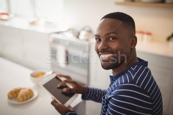 Sorridente homem digital comprimido cozinha retrato Foto stock © wavebreak_media