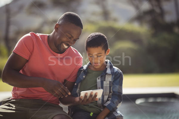 Son and father using mobile phone near poolside Stock photo © wavebreak_media