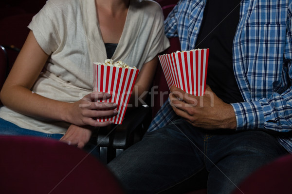Mid section of couple having popcorn while watching movie in theatre Stock photo © wavebreak_media