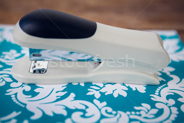 Close up of stapler on blue patterned paper at table Stock photo © wavebreak_media