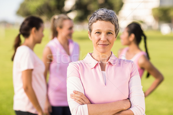 Woman wearing pink for breast cancer in front of friends Stock photo © wavebreak_media
