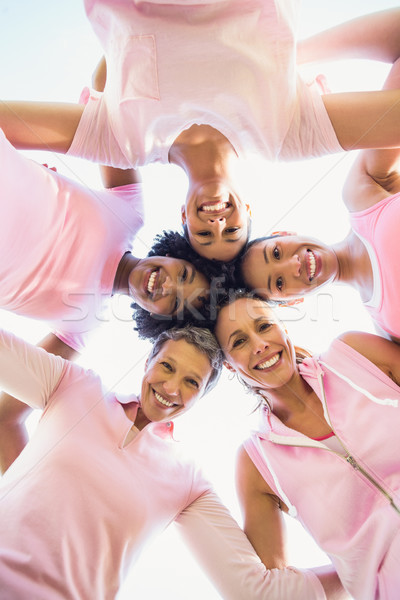 Women wearing pink for breast cancer with arms around Stock photo © wavebreak_media