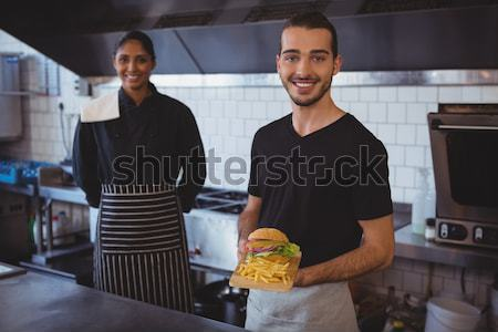 Portrait of waiter with coworker holding food tray in cafe Stock photo © wavebreak_media