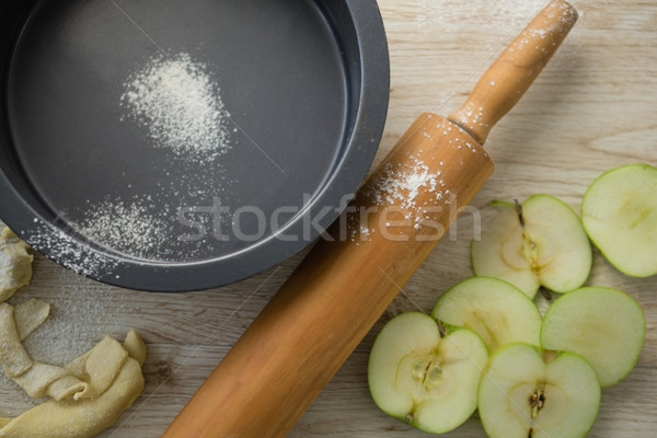 Overhead view of rolling pin by apple slices and container Stock photo © wavebreak_media