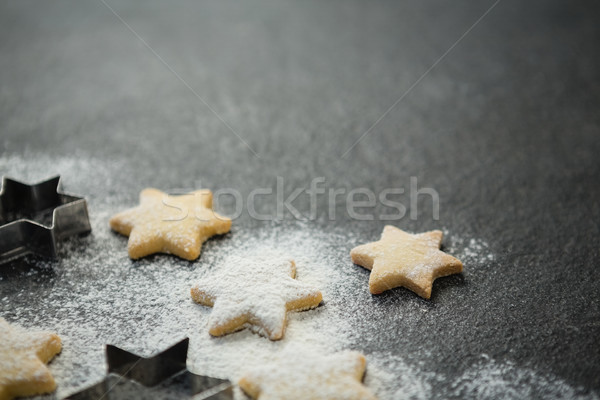 Close up of star shape cookies with pastry cutter Stock photo © wavebreak_media
