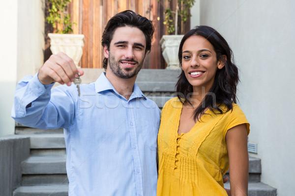 Happy couple in front of new house showing keys Stock photo © wavebreak_media