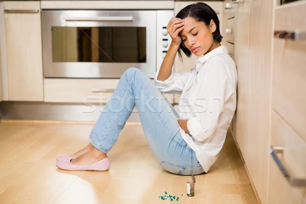 Upset bunette sitting on the floor with bottle of pills Stock photo © wavebreak_media