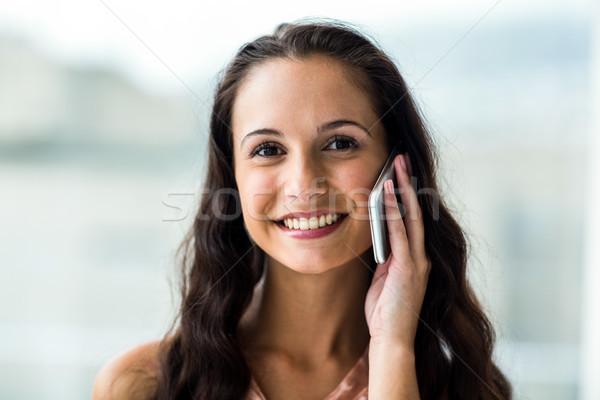 Smiling woman on phone call looking at camera Stock photo © wavebreak_media