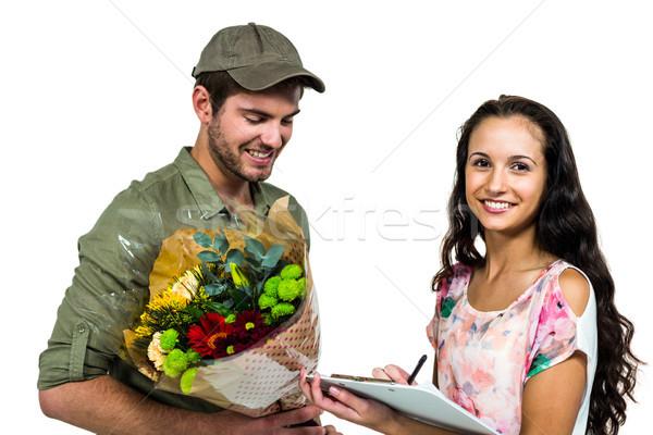 Frau Unterzeichnung Bouquet Lieferung lächelnd Briefträger Stock foto © wavebreak_media