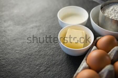 Beaten eggs, egg tray, butter, oil and flour kept on a black surface Stock photo © wavebreak_media