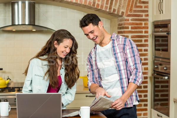 Happy couple reading newspaper in kitchen Stock photo © wavebreak_media