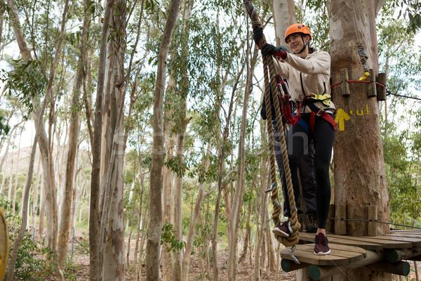 Woman wearing safety helmet getting ready to climb on zip line Stock photo © wavebreak_media
