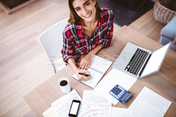 Portret uśmiechnięta kobieta piśmie notatnika laptop Zdjęcia stock © wavebreak_media