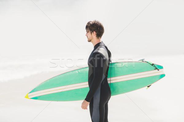 Férfi tart szörfdeszka tengerpart napos idő tenger Stock fotó © wavebreak_media