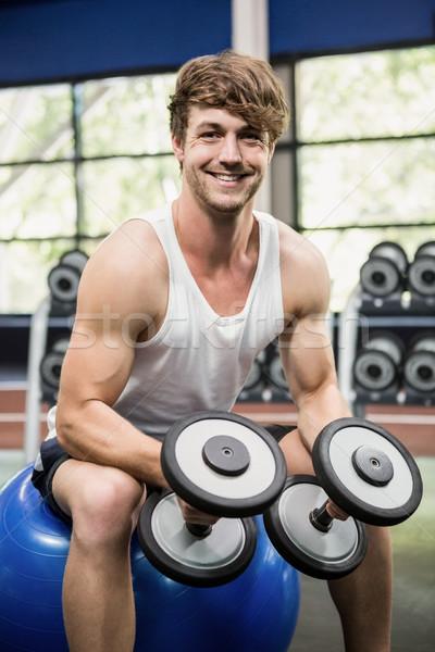 Man sitting on fitness ball and lifting dumbbells Stock photo © wavebreak_media