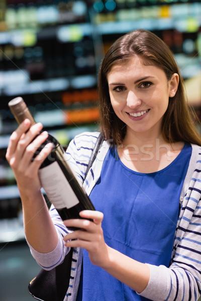 Nő tart borosüveg áruház üzlet bor Stock fotó © wavebreak_media