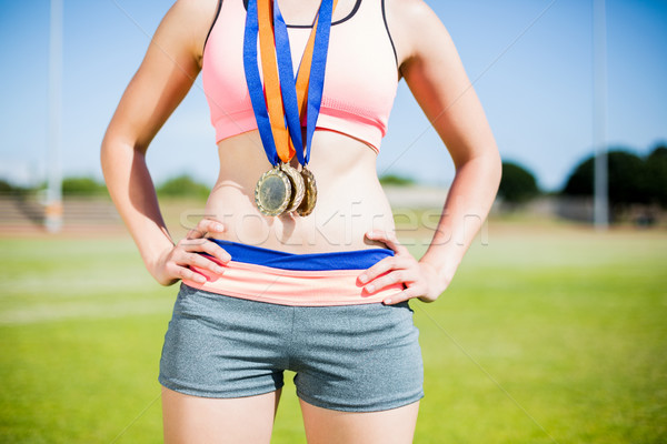 Stock photo: Mid section of female athlete with gold medals around her neck