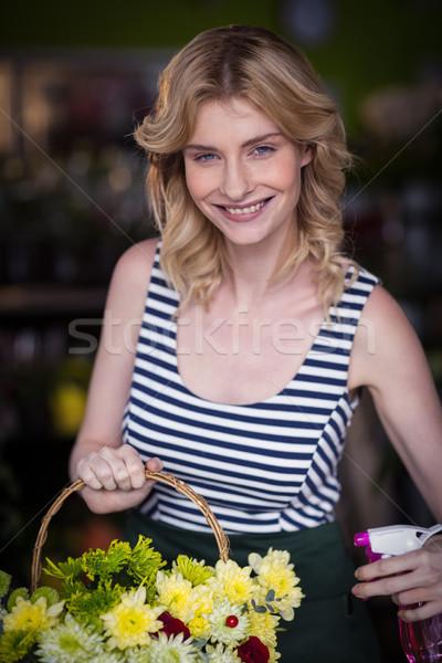 Female florists spraying water on flowers in flower shop Stock photo © wavebreak_media