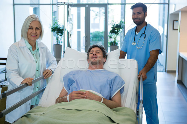 Portrait of doctors standing while patient lying on emergency stretcher Stock photo © wavebreak_media