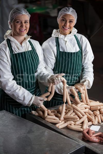 Female butchers processing sausages Stock photo © wavebreak_media