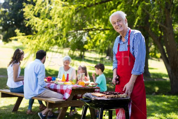 Senior man barbequing with family in background Stock photo © wavebreak_media