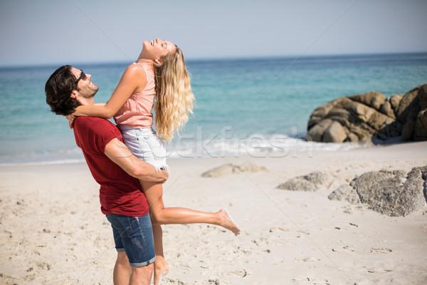 Boldog fiúbarát hordoz barátnő áll tengerpart Stock fotó © wavebreak_media