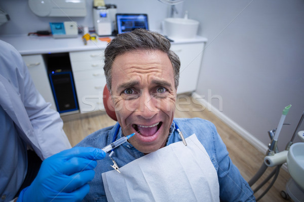 Dentist injecting anesthetics in scared male patient mouth Stock photo © wavebreak_media