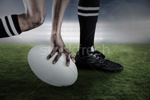 Composite image of low section of athlete holding ball while running Stock photo © wavebreak_media