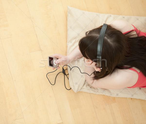 Brunette vrouw luisteren muziek vloer Stockfoto © wavebreak_media