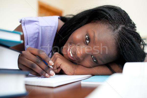 Cheerful teen girl doing her homework Stock photo © wavebreak_media