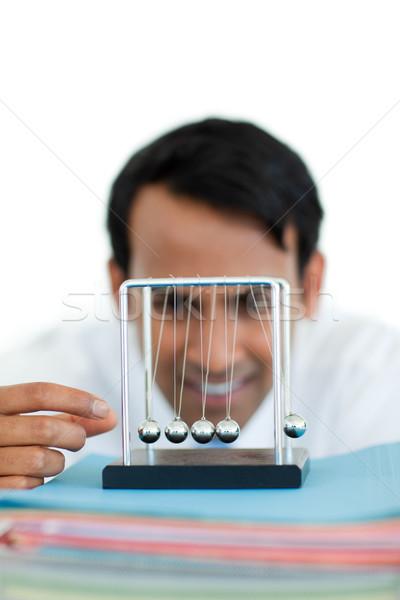 Ethnic businessman playing with kinetic balls Stock photo © wavebreak_media