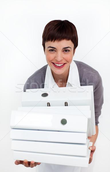 Smiling businesswoman putting a stack of folders on a desk  Stock photo © wavebreak_media