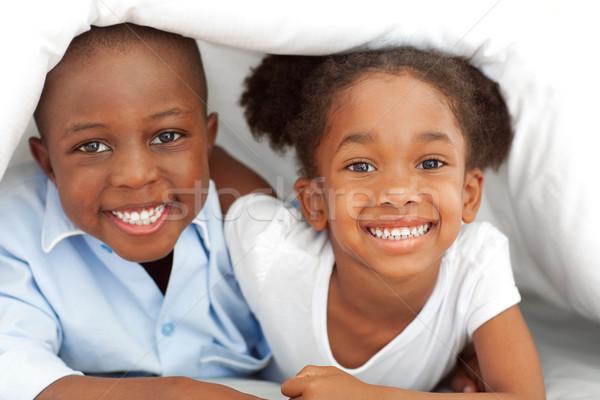Portrait of ethnic siblings lying down on bed Stock photo © wavebreak_media